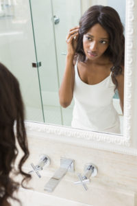 Young woman looking her self in mirror of the bathroom