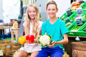 Children selecting vegetables while organic grocery shopping in supermarket